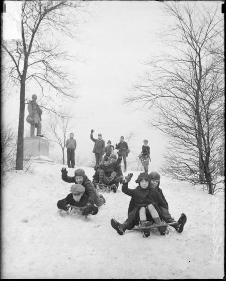 Children waving as they sled down a hill in Chicago, Illinois, 1929.
